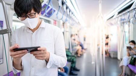 Asian man wearing surgical face mask using smartphone on skytrain or urban train.   coronavirus (COVID-19) outbreak prevention in public transportation. Health awareness for pandemic protection