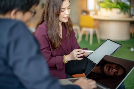 Business meeting and teamwork concept. Asian businesswoman explaining project data report to colleagues using digital tablet for presentation at workplace. Coworkers team brainstorming ideas in office