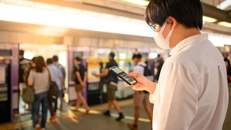 Asian man wearing surgical face mask using smartphone at skytrain station platform. coronavirus (COVID-19) outbreak prevention in public transportation. Health awareness for pandemic protection
