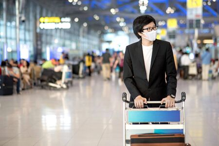 Asian businessman wearing suit and face mask walking with airport trolley and suitcase luggage in airport terminal. Coronavirus (COVID-19) outbreak prevention. Health awareness for pandemic protection