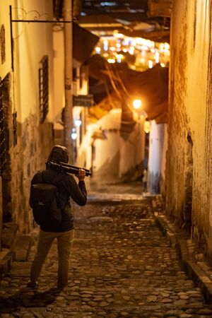 Hoody photographer man holding tripod standing in alley in Cusco (Cuzco), Peru. Historical inca empire city exploration at night. Mystery city concept