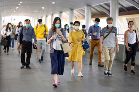 THAILAND, BANGKOK - MARCH 16, 2020 : Crowded people wearing face mask for protect Coronavirus (COVID-19) outbreak and PM2.5 air pollution walking on urban walkway in rush hour.