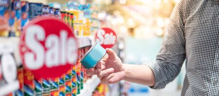 Asian man customer choosing canned food from shelf in supermarket or grocery store. Hoard instant food for quarantine at home during Coronavirus (COVID-19) pandemic. Consumerism concept Reklamní fotografie