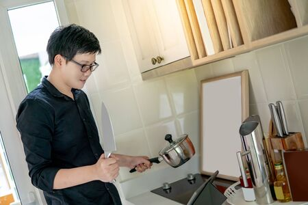 Asian man watching cooking tutorial on digital tablet learning how to cook food in the kitchen. Domestic life during quarantine. Stay home concept 写真素材