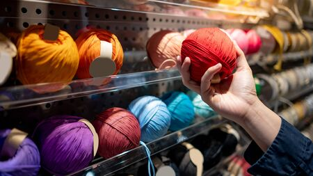 Male hand choosing red yarn ball in knitting shop or needlework shop. Selection of colorful yarn wool on shopfront. Shopping lifestyle concept