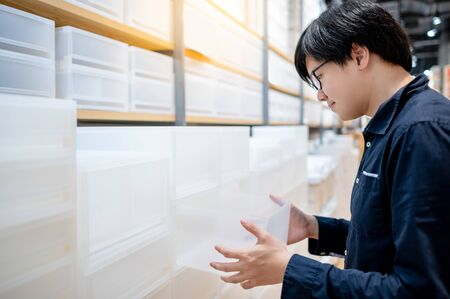 Asian man customer choosing white plastic box drawer from product shelf in furniture store. Home decoration shopping concept 免版税图像