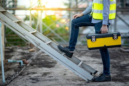 Asian maintenance worker man with safety helmet and green vest carrying tool box climbing on aluminium ladder at construction site. Civil engineering, Architecture builder and building service concepts