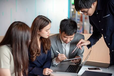 Business meeting and teamwork concept. Asian colleagues discussing about project report using laptop computer and digital tablet at workplace. Coworkers team brainstorming ideas in office boardroom. Stock Photo
