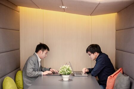 Two Asian businessman working with laptop computer sitting together in meeting room. Office workers having a discussion about project plan. Business conference concept