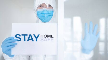 Doctor or medical worker in personal protective equipment (PPE) suit, mask and gloves showing paper with message 'Stay home Stay safe'. Quarantine campaign during Coronavirus (COVID-19) pandemic.