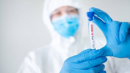 Medical scientist man in personal protective equipment suit (PPE), mask and gloves holding COVID-19 Test tube in hospital laboratory. Male doctor getting result of Coronavirus case. 2019-nCoV research