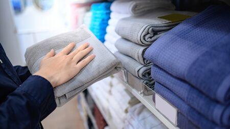 Buying new towel concept. Male hand customer choosing gray (grey) towel form display rack in cloth shop. Reklamní fotografie