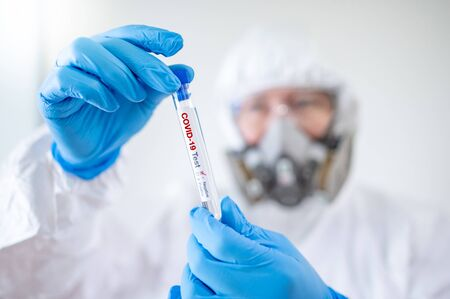Medical scientist man in biohazard chemical protective suit (PPE), mask and goggles holding COVID-19 Test tube in hospital laboratory. Male doctor or physician getting result of Coronavirus case.