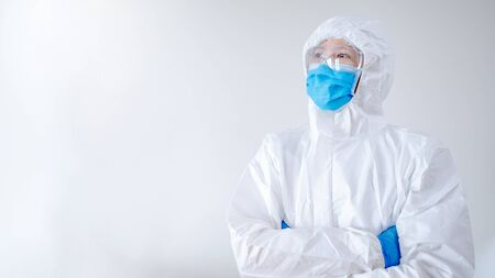 Doctor or physician in personal protective equipment standing with arms crossed posing in hospital clinic. Medical worker wearing PPE suit, mask and goggles for preventing Coronavirus (COVID-19).