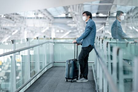 Asian man tourist wearing face mask carrying suitcase luggage waiting in airport terminal gate hall. Coronavirus (COVID-19) pandemic prevention when travel. Health awareness and social distancing Foto de archivo