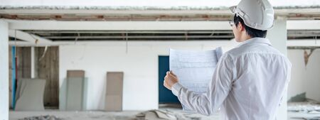 Asian civil engineer or construction worker man wearing protective safety helmet holding blueprints. Male architect working at construction site. Building and architecture design concepts