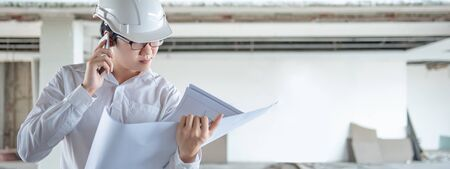 Asian civil engineer or construction worker man using phone while reading blueprints. Male architect checking architectural drawing at construction site. Building project management concept Stockfoto