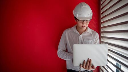 Asian civil engineer or construction worker man wearing protective safety helmet holding laptop computer. Male architect working near red wall at construction site. Architecture concept