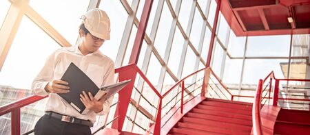 Asian civil engineer or construction worker man wearing protective safety helmet holding document file. Male architect working on red stair at construction site. Building and architecture concept Reklamní fotografie
