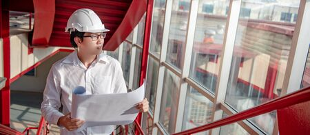 Asian civil engineer or construction worker man wearing protective safety helmet holding blueprints. Male architect working on red stair at construction site. Building and architecture design concepts