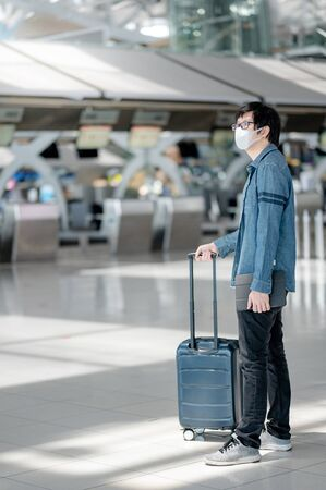 Asian man tourist wearing face mask carrying suitcase luggage waiting for check-in in airport terminal. Coronavirus (COVID-19) pandemic prevention when travel. Health awareness and social distancing