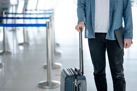 Travel insurance concept. Male tourist carrying suitcase luggage and digital tablet waiting for check in and baggage claim at airline counter in airport terminal.
