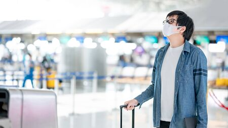 Asian man tourist wearing face mask carrying suitcase luggage at check-in counter in airport terminal. Coronavirus (COVID-19) pandemic prevention when travel. Health awareness and social distancing
