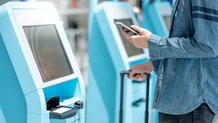 Male tourist holding passport and smartphone using self check-in kiosk in airport terminal. Travel abroad concept Zdjęcie Seryjne - 150499947