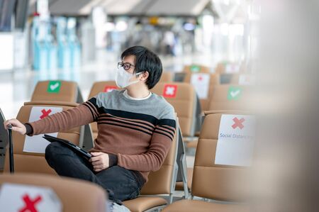 Asian man tourist with suitcase luggage wearing face mask using digital tablet in airport terminal. Coronavirus (COVID-19) prevention when travel abroad. Health awareness and social distancing concept