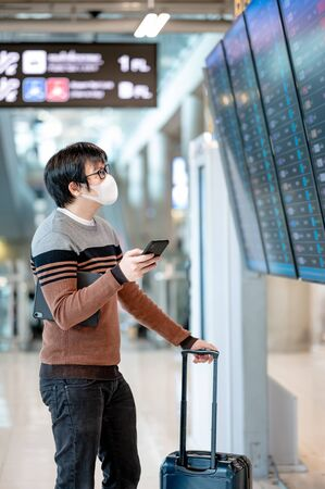 Asian man tourist wearing face mask checking flight from arrival departure board using smartphone in airport terminal. Coronavirus (COVID-19) pandemic prevention when travel. Social distancing concept