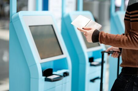Male tourist holding passport and smartphone using self check-in kiosk in airport terminal. Travel abroad concept Zdjęcie Seryjne