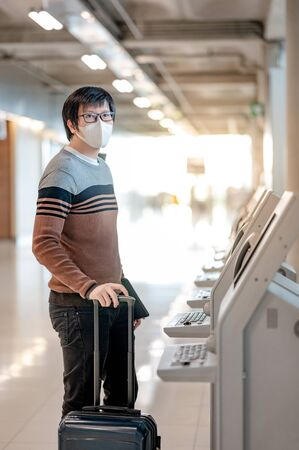 Asian man tourist wearing face mask using self check-in kiosk in airport terminal. Coronavirus (COVID-19) pandemic prevention when travel abroad. Health awareness and social distancing concept Zdjęcie Seryjne