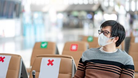 Asian man tourist wearing protective face mask sitting in airport terminal. Coronavirus (COVID-19) prevention when travel abroad. Health awareness and social distancing