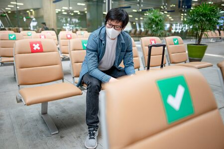 Asian man tourist wearing protective face mask sitting with suitcase luggage in airport terminal. Coronavirus (COVID-19) pandemic prevention when travel abroad. Health awareness and social distancing Zdjęcie Seryjne