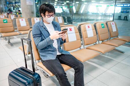 Asian man tourist with suitcase luggage wearing face mask using smartphone in airport terminal. Coronavirus (COVID-19) pandemic prevention when travel abroad. Health awareness and social distancing