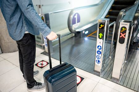 Travel insurance concept. Male tourist carrying suitcase luggage at escalator in airport terminal.