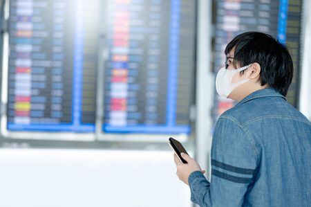 Asian man tourist wearing face mask holding smartphone and passport at arrival departure board in airport terminal. Coronavirus (COVID-19) pandemic prevention when travel. Social distancing concept