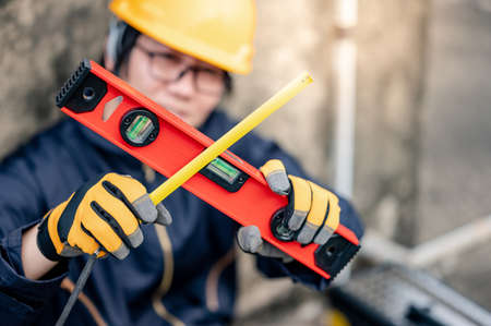 Maintenance worker man or male Asian mechanic wearing protective suit and helmet holding tape measure and level tool in cross shape at construction site. Equipment for civil engineering project