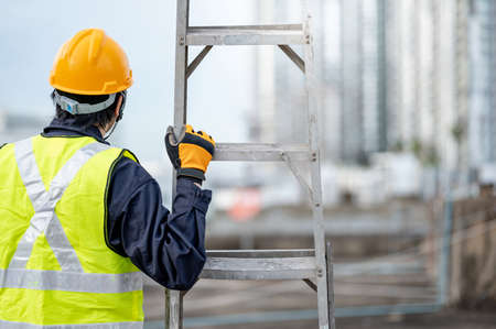 Asian maintenance worker man with safety helmet and green vest carrying aluminium step ladder at construction site. Civil engineering, Architecture builder and building service concepts Zdjęcie Seryjne - 150889977