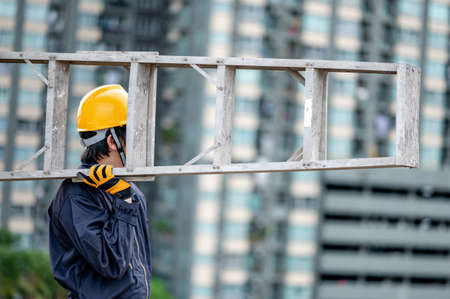 Asian maintenance worker man with protective suit and safety helmet carrying aluminium step ladder at construction site. Civil engineering, Architecture builder and building service concepts Zdjęcie Seryjne