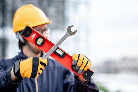 Male Asian mechanic or maintenance worker man wearing protective suit and helmet holding wrench and level tool in cross shape at construction site. Equipment for mechanical engineering project Zdjęcie Seryjne