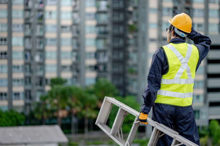 Asian maintenance worker man with safety helmet and green vest carrying aluminium step ladder at construction site. Civil engineering, Architecture builder and building service concepts Banque d'images - 150889840
