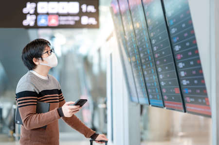 Asian man tourist wearing face mask checking flight from arrival departure board using smartphone in airport terminal. Coronavirus (COVID-19) pandemic prevention when travel. Social distancing concept Zdjęcie Seryjne - 151900796