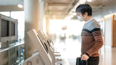 Asian man tourist wearing face mask using self check-in kiosk in airport terminal. Coronavirus (COVID-19) pandemic prevention when travel abroad. Health awareness and social distancing concept Publikacyjne
