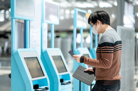 Asian man tourist wearing face mask using self check-in kiosk in airport terminal. Coronavirus (COVID-19) pandemic prevention when travel abroad. Health awareness and social distancing concept
