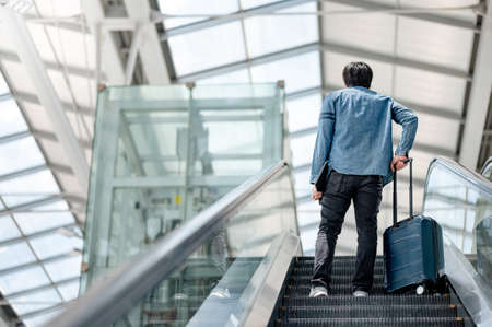 Travel insurance concept. Asian man tourist carrying suitcase luggage and digital tablet on escalator in airport terminal. Imagens