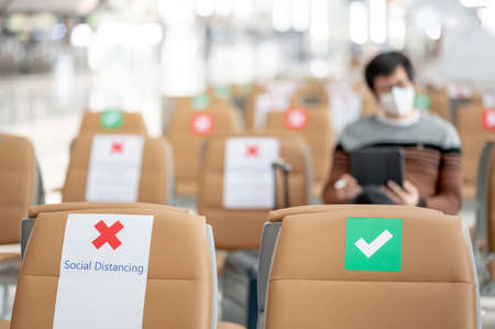 Social distancing or physical distancing concept. Correct and cross symbol on seat at waiting area of airport terminal. Guidance sticker show to keep distance while sitting public building.