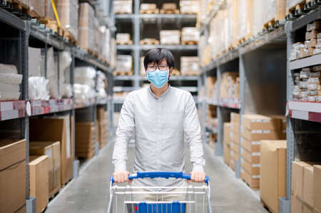 Asian man customer wearing face mask shopping with shopping cart in grocery store or supermarket. Preventing spread of COVID-19 (Coronavirus) when buying goods. New normal concept