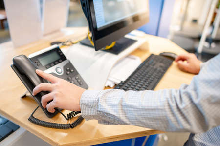 Male customer support operator hand trying to response customer call by using landline phone on working desk in office. Call center business concept Archivio Fotografico