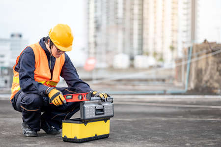 Male Asian mechanic or maintenance worker man wearing protective suit and helmet opening work tool box at construction site. Equipment for mechanical engineering project Stok Fotoğraf